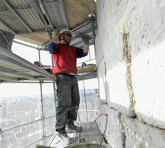 Photo d'un ouvrier en train de restaurer la façade de la Citadelle de Besançon